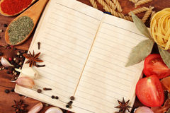 Notebook for recipes and spices. On wooden table Stock Image