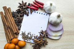 Notebook for recipes. And spices on wooden table Royalty Free Stock Photo