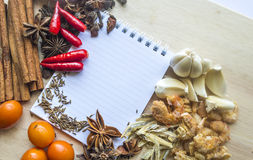 Notebook for recipes. And spices on wooden table Royalty Free Stock Image