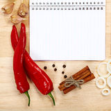 Notebook for recipes, vegetables and spices. Notebook for recipes, vegetables and spices on wooden table Royalty Free Stock Photography