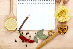 Notebook for recipes, vegetables and spices on wooden table.  Royalty Free Stock Photography