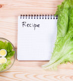 Notebook with recipes and vegetables. On a wooden board Stock Photo