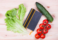 Notebook with recipes and vegetables. On a wooden board Stock Photos