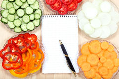 Notebook for recipes and vegetables on wooden table.  Royalty Free Stock Photos