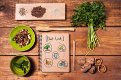 Notebook for recipes, walnuts, parsley and seeds on wooden table. Notebook for recipes, pencil, walnuts, parsley and seeds on wooden table. Diet concept Royalty Free Stock Photo