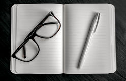 Notebook with red bookmark on a dark table with a pen and glasses Royalty Free Stock Photography