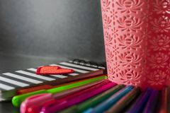 Notebook  with red heart and a basket with color pens on drak table and background. Notebook cover with red heart and a basket with color pens. Dark table and stock photo