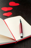 Notebook with red pen and hearts Stock Image