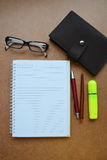 Notebook, red pen, wooden pencil, marker pen, eye glasses on wooden background Stock Photography