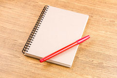 Notebook and red pen on wooden table.education. Stock Photos