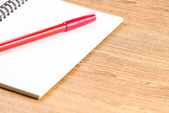 Notebook and red pen on wooden table.education. Royalty Free Stock Images