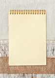 Notebook, ribbon and linen fabric on the old wooden background Stock Photography
