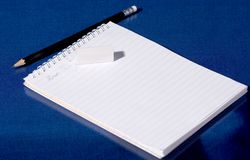 Notebook, rubber and pencil. A copybook, a rubber and a graphite pencil on blue background Royalty Free Stock Images