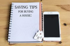 Notebook with Saving Tips for Buying Home. Notebook with Home Buying Tips Text,White Wooden Houses Models and Phone stock photography