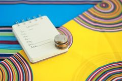 Notebook with coins on colorful background stock photos