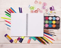 Notebook and school supplies on desk. Top view of open blank notebook with school supplies on wooden desk stock images