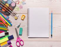 Notebook with school supplies. Top view of blank notebook with school supplies on wooden desk stock image