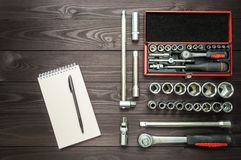 Notebook and set of tools for an auto mechanic on a dark wooden workbench stock photo