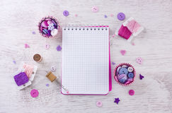 Notebook with sewing items.  a check fabrics, buttons, thread and pins Royalty Free Stock Photos