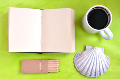 Notebook, shell, cup of coffee and pastels on green background Royalty Free Stock Photo