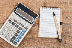 Notebook showing empty page and calculator. On wooden desk royalty free stock images
