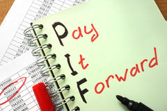 Notebook with  sign Pay It Forward PIF. Stock Photo