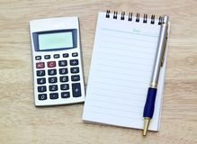 Notebook, silver ballpen and calculator Stock Photo