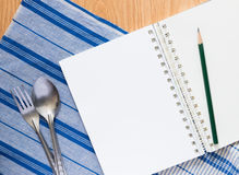 Notebook , silver spoon and fork Stock Image