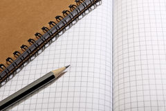 A notebook and a simple pencil lie on a blank sheet of paper. Close-up. Royalty Free Stock Image