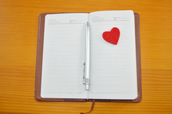 Notebook and a small red heart on a table Royalty Free Stock Image