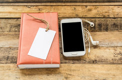 Notebook,smart phone and earphone on wooden table Royalty Free Stock Photo