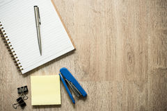 Notebook with some office stationery supplies on wood background Royalty Free Stock Images