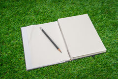 Notebook on spring green grass. Royalty Free Stock Images