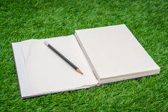 Notebook on spring green grass. Stock Photo