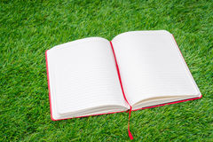 Notebook on spring green grass. Royalty Free Stock Image