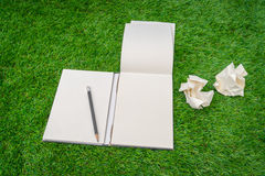 Notebook on spring green grass. Royalty Free Stock Photography