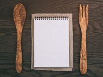 Notebook with spring on wood table with wooden utensils for recipe Royalty Free Stock Image