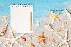 Notebook, starfishes and seashells on sand background top view. Planning summer holidays, trip, travel and vacation concept. royalty free stock images