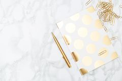 Notebook and stationery items of gold color. Feminine desktop. Notebook and stationery items of gold color. Desktop royalty free stock image