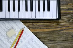 notebook with a stave, pencils with an eraser, a piano keyboard on a wooden background