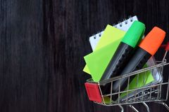 Notebook, stickers and highlighters in a shopping cart royalty free stock images