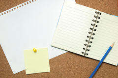 Notebook and sticky note on cork board Royalty Free Stock Images
