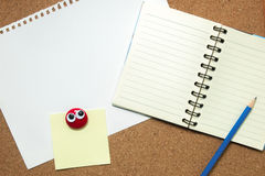 Notebook and sticky note on cork board Royalty Free Stock Photography