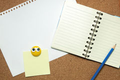 Notebook and sticky note on cork board Stock Image