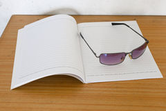 Notebook and sunglasses. On the plywood table Royalty Free Stock Images