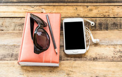 Notebook,sunglasses,smart phone and earphone on wooden table Stock Photos