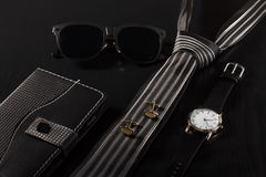 Notebook, Sunglasses, Tie, Cuff-links, Watch On A Black Backgrou Royalty Free Stock Image