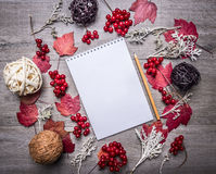 Notebook surrounded autumn decorations, leaves, berries, balls made of rattan, place for text,frame wooden rustic background to Royalty Free Stock Photography