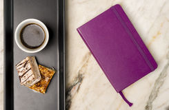 Notebook, sweets and black coffee. On a white marble surface Royalty Free Stock Images
