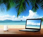 Notebook on table and beach. Notebook on table and tropical beach Stock Photography